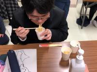 水で作った非常食のラーメンを食べる男子生徒