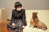 彫刻作品の隣に腰掛けて鑑賞する様子