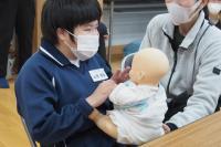 赤ちゃんの人形を抱く女子生徒