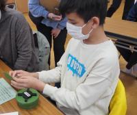 地雷の模型を触る男子児童